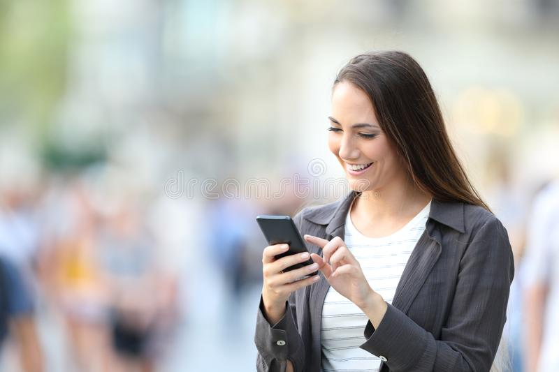 Happy casual woman checking smart phone content royalty free stock image