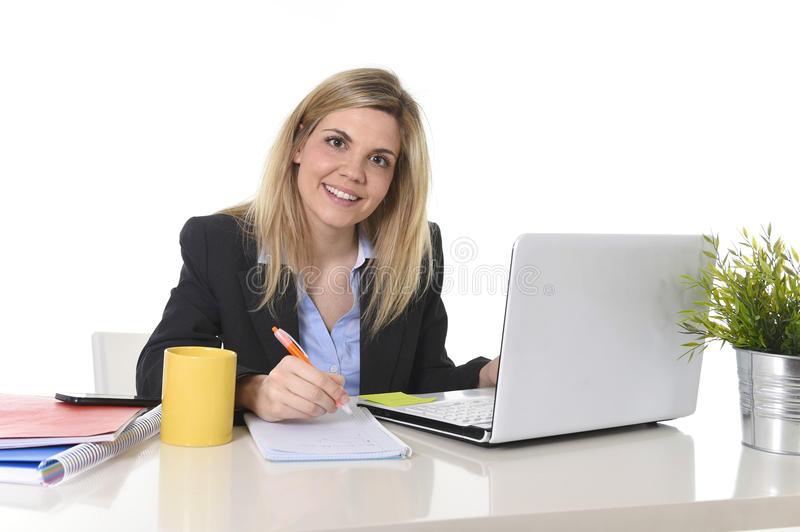 Happy Caucasian blond business woman working on laptop computer at modern office desk stock photography