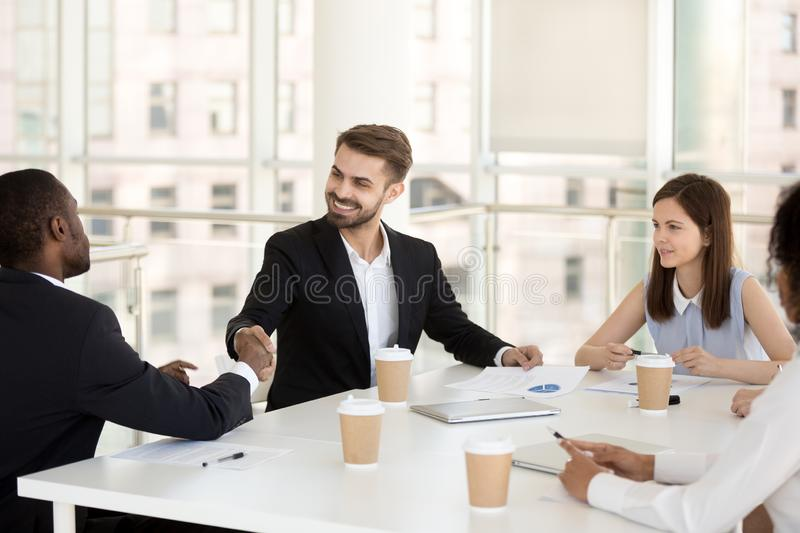 Happy caucasian businessman shake hand of african partner at mee. Happy friendly caucasian businessman shake hand of african partner greeting, closing deal royalty free stock photo