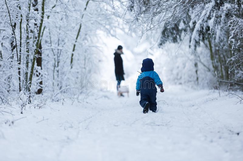 Happy caucasian child playing in snow. Boy playing in big snow in winter. Happy caucasian child playing in snow stock photo