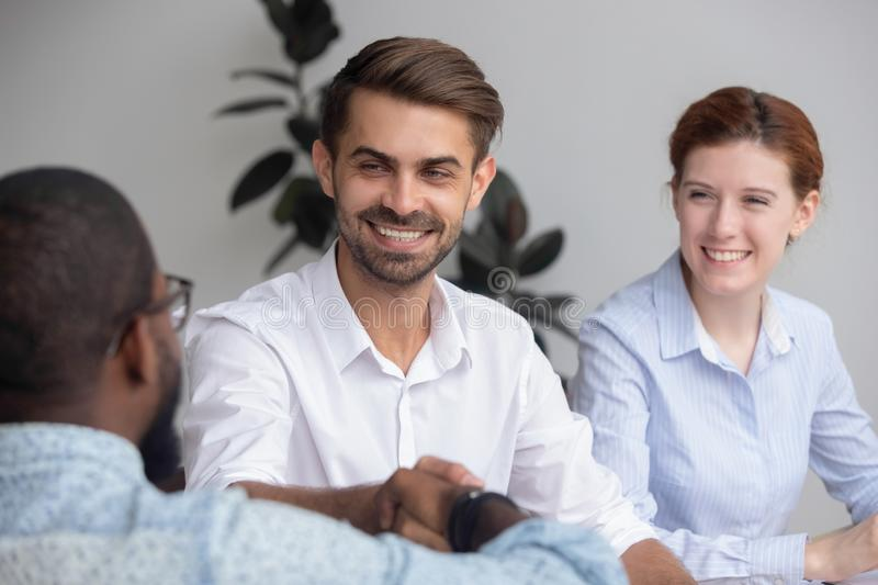 Happy caucasian hr manager handshake hire employ african american candidate royalty free stock photo