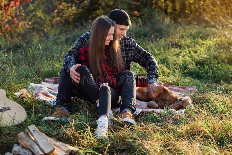 Happy caucasian couple with guitar resting on picnic in spring park. Young man and his girlfriend playing with their royalty free stock photos