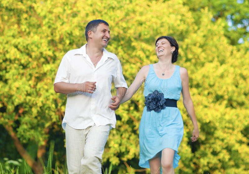 Happy caucasian Couple Having Good Time Outdoors Walking Joined Hands. Mature Couple Relationships Concepts and Ideas. Happy caucasian Couple Having Good Time royalty free stock photography
