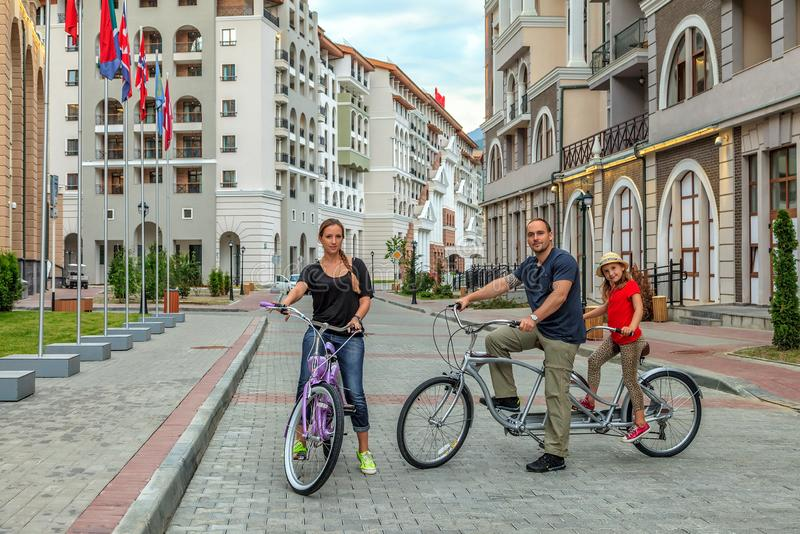 Happy Caucasian family of father, mother and daughter posing for camera outdoors in the street at summer on buildings background royalty free stock photo