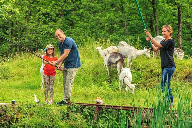 Happy Caucasian family of three people fishing together by a pond while having vacation at countryside royalty free stock photography