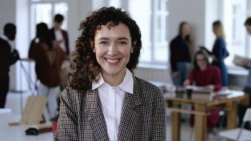 Happy Caucasian female corporate employee in elegant formal suit with curly hair smiling cheerfully at modern office. stock photography