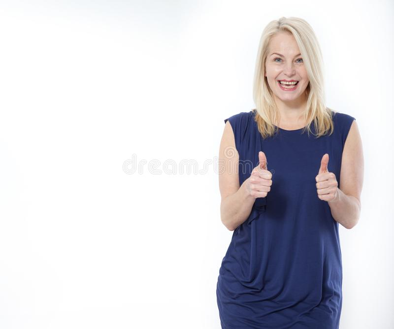 Happy caucasian female wearing dress making thumb up sign and smiling cheerfully, showing her support and respect to stock photo