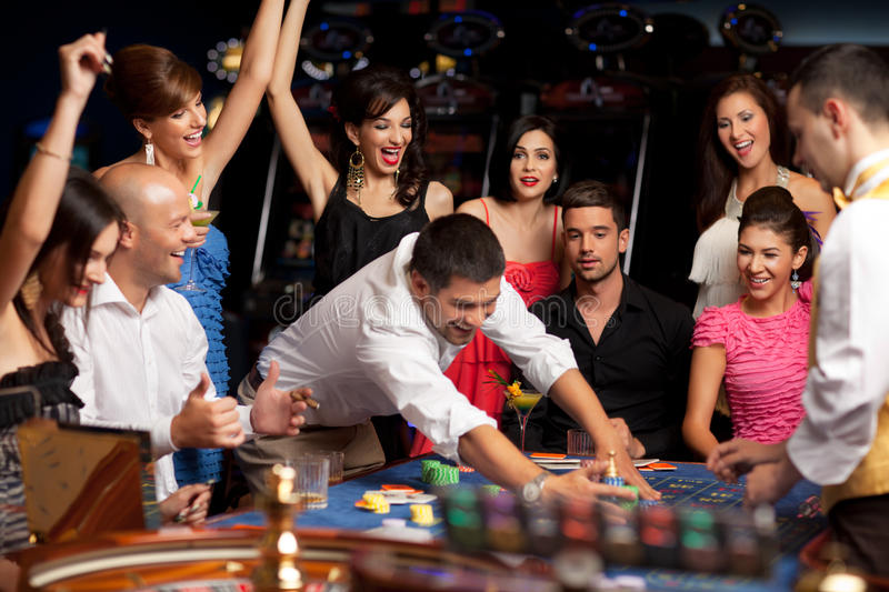 Happy caucasian friends playing roulette in casino stock photos