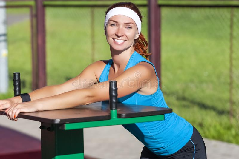 Happy Caucasian Ginger Female in Sport Outfit with Armwrestling. Sport Ideas. Happy Caucasian Ginger Female in Sport Outfit with Armwrestling Trainer Outdoors stock photos