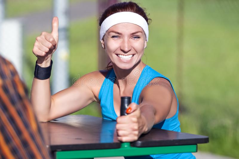 Happy Caucasian Ginger Female in Sport Outfit with Armrestling. Happy Caucasian Ginger Female in Sport Outfit with Armwrestling Trainer Outdoors. showing Thumbs stock photography