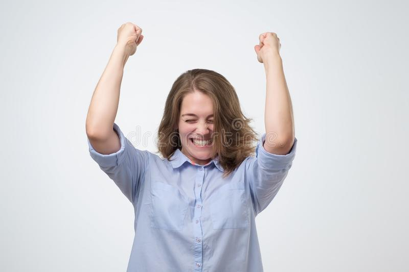 Happy caucasian girl with her fists up. Isolated on white wall. Positive facial human emotion royalty free stock images