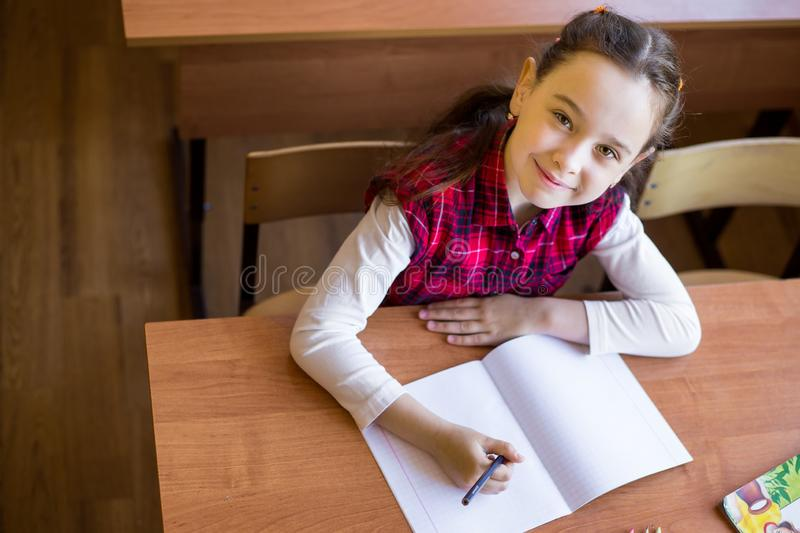 Happy caucasian girl sitting at desk in class room and begins to draw in a pure notebook. Preparation for exams, tests.  stock image