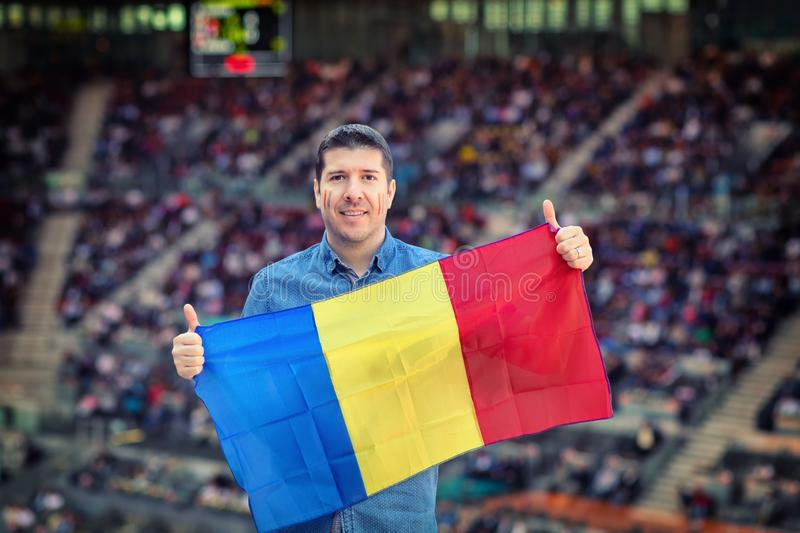 Happy caucasian man holding Romanian national flag in hands at international sport event – supporter at stadium cheering. Happy caucasian man holding royalty free stock photography