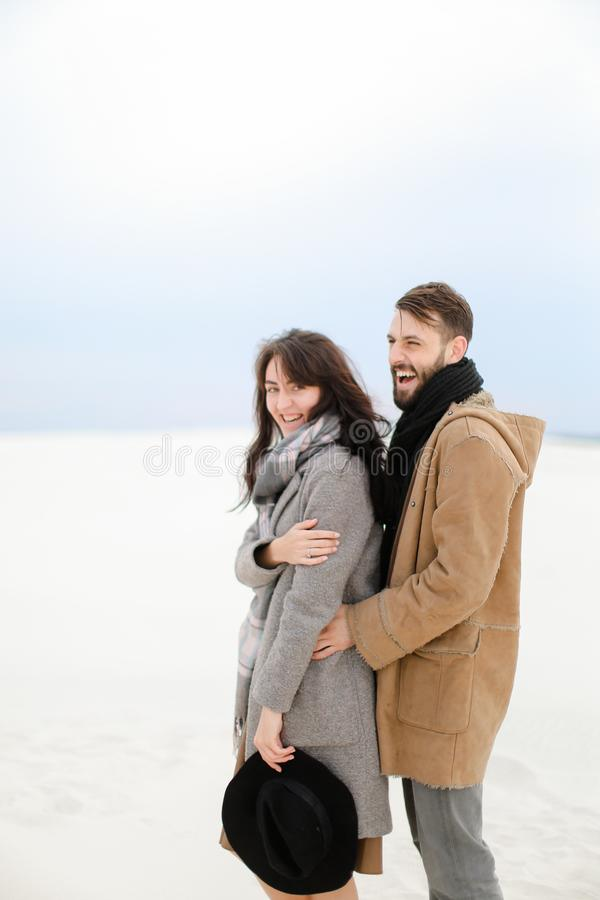 Happy caucasian man hugging female person wearing grey coat and scarf, white winter monophonic background. Happy caucasian men hugging female person wearing stock photos