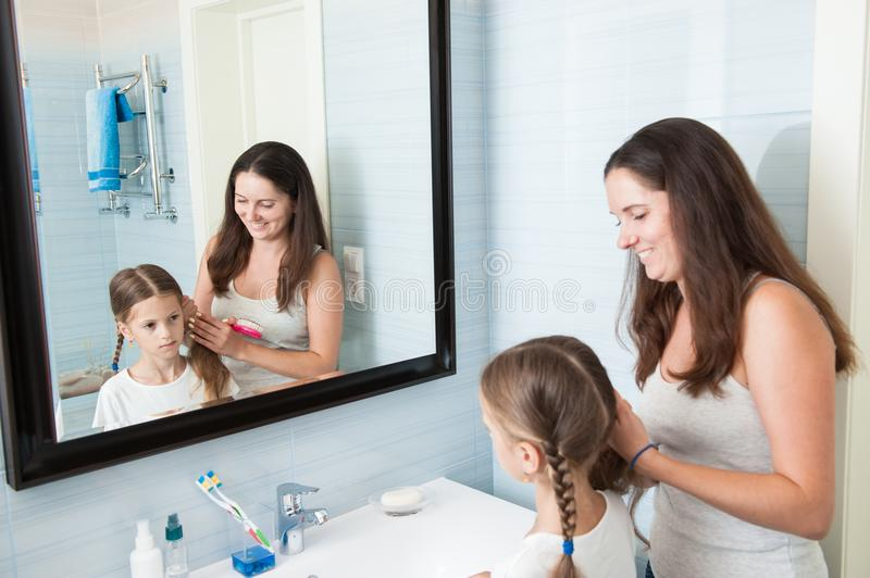 Happy mother braid pigtails to sad daughter in bathroom morning. Happy caucasian mother braid pigtails to sad daughter in bathroom morning hygiene care stock photography