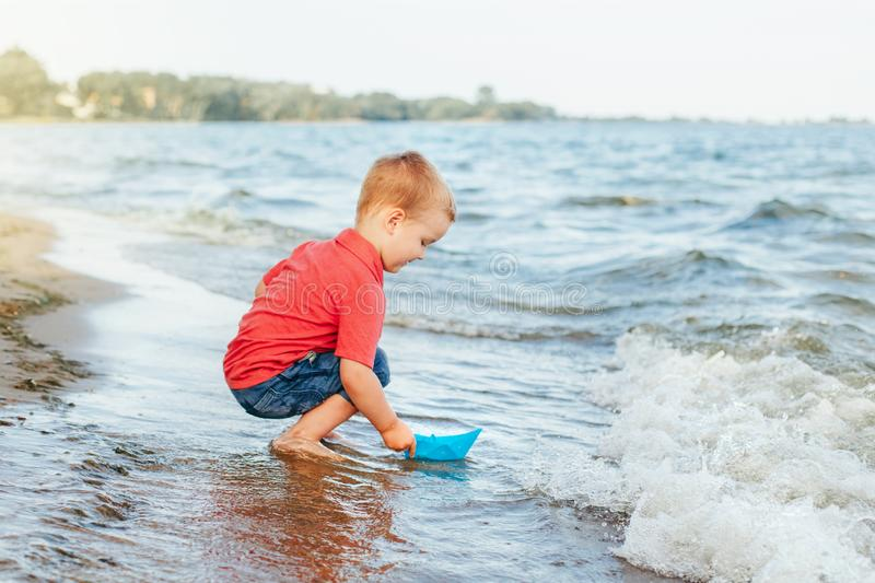 Happy Caucasian red-haired toddler child boy putting blue paper boat in water on lake sea ocean royalty free stock photography