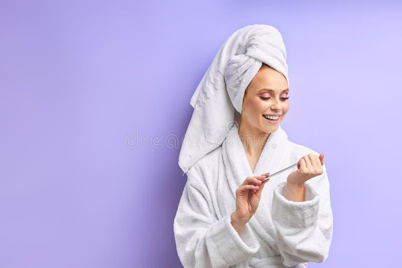 Happy caucasian woman in bathrobe trims nails royalty free stock photography