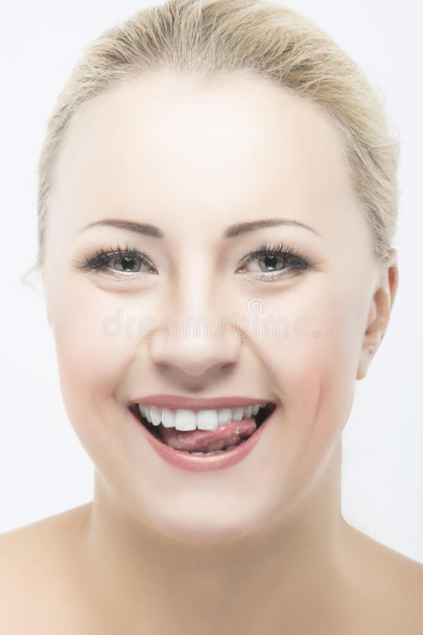 Happy Caucasian Woman Beauty Face Closeup Portrait. Touching Shiny White Teeth with Tongue royalty free stock image
