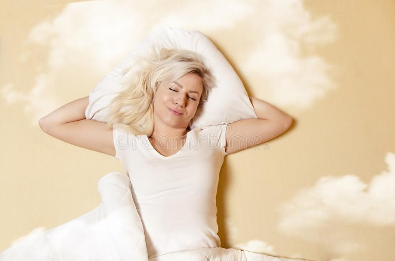 Happy Caucasian woman enjoying in good sleep. Sleeping in clouds stock photography