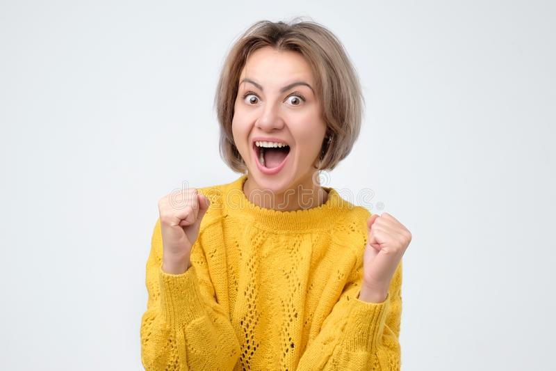 Happy caucasian woman raising fists in winning gesture and celebrating success royalty free stock photo