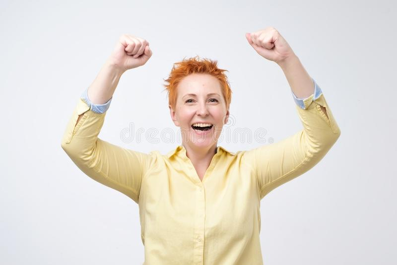 Happy caucasian woman with red hair exults pumping fists ecstatic celebrates success stock photo