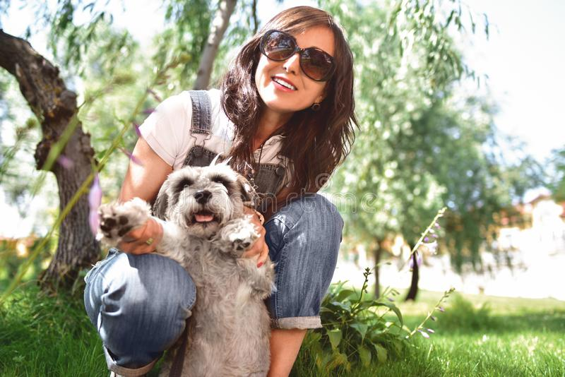 Happy caucasian woman in sunglasses resting in nature with her beloved dog schnauzer. concept of love for animals. best friends stock photo
