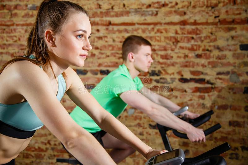 Happy caucasian woman and man on exercise bikes in health club. stock photography