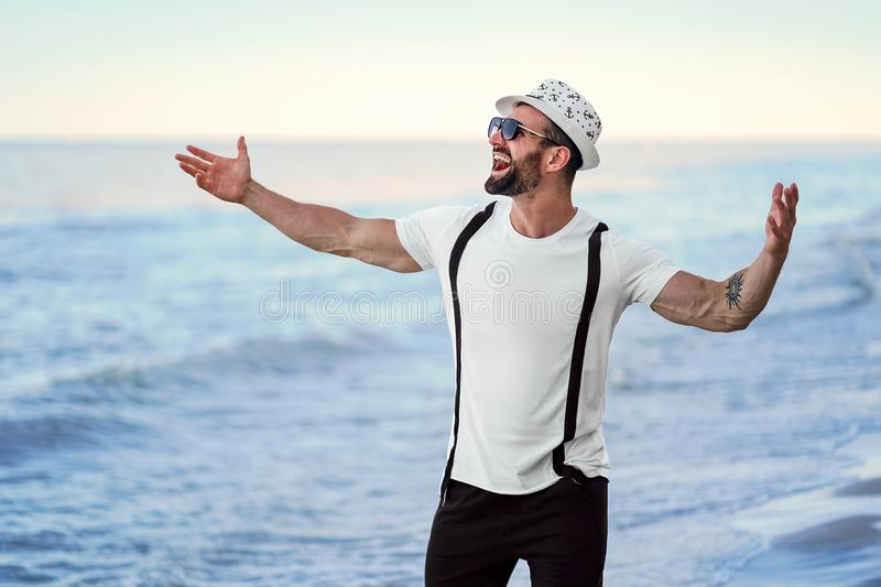Happy celebrating bearded man in hat and sunglasses posing with hands up at the resort on the sea background royalty free stock photos