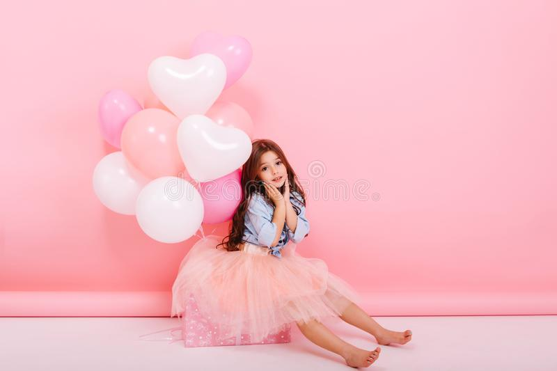 Happy celebration of birthday party with flying balloons of charming cute little girl in tulle skirt sitting on box. On pink background. Expressing true royalty free stock photo
