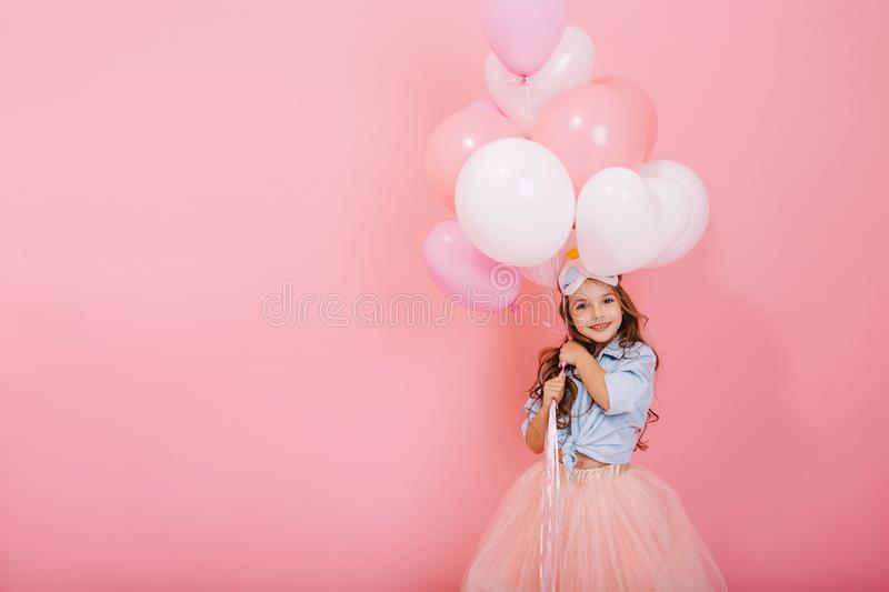 Happy celebration of birthday party with flying balloons charming cute little girl in tulle skirt smiling to camera royalty free stock photography