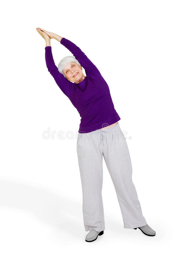 Happy charming beautiful elderly woman doing exercises while working out playing sports stock photography