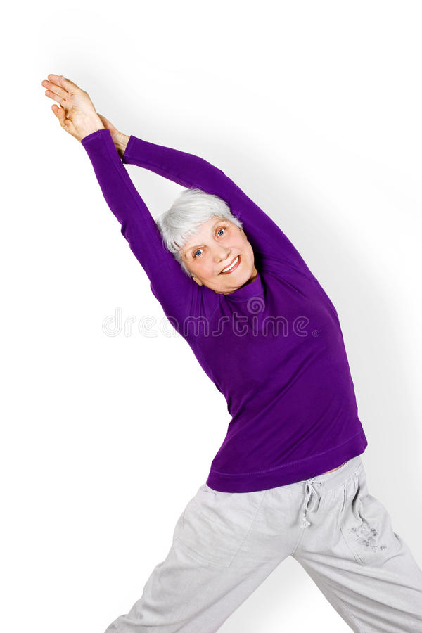 Happy charming beautiful elderly woman doing exercises while working out playing sports. stock images
