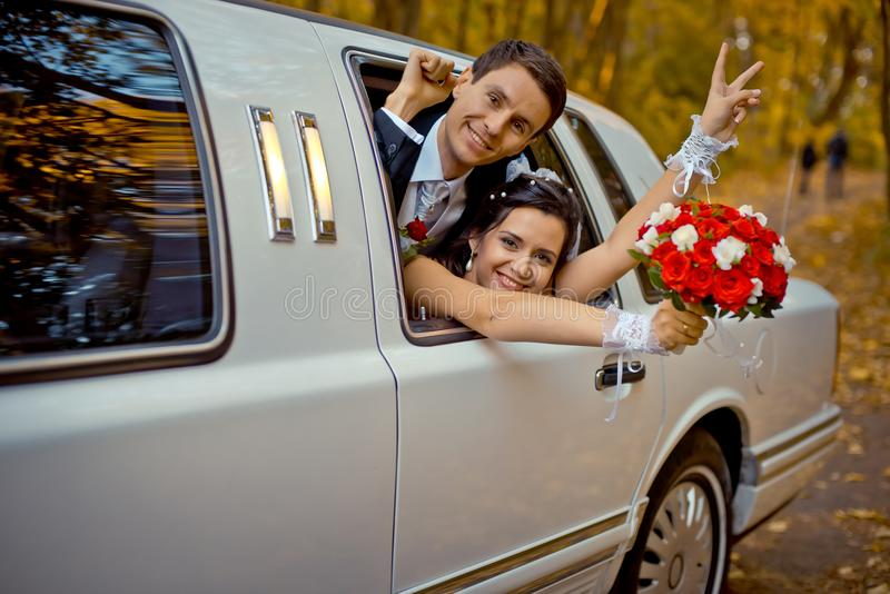Happy charming newlywed couple is looking through the car window. The bride with the wedding bouquet of red roses is stock photography
