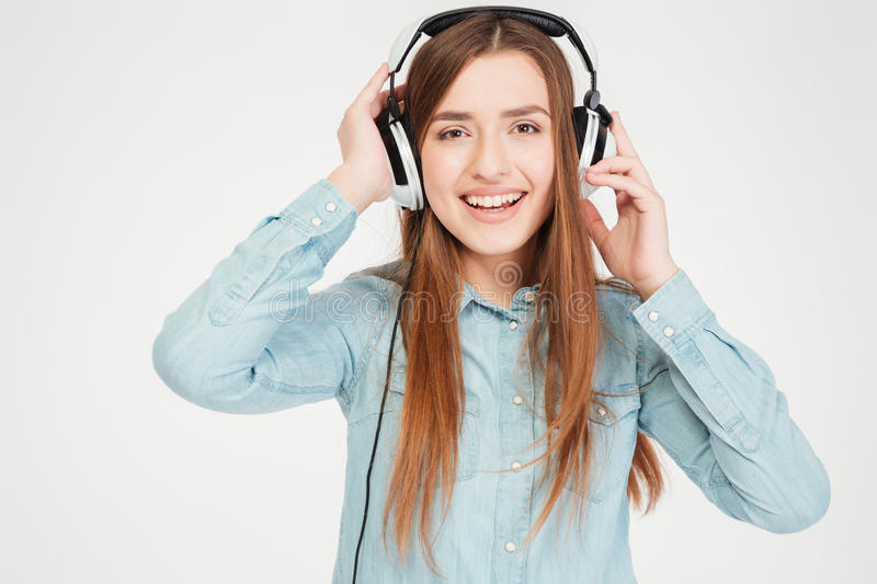 Happy charming young woman in headphones listening to music stock image