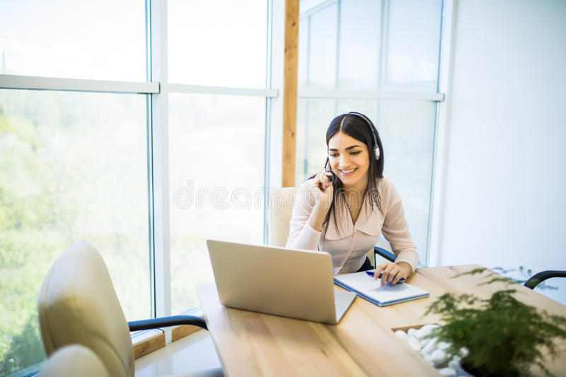 Happy charming young woman sitting and working with laptop using headset in office royalty free stock image