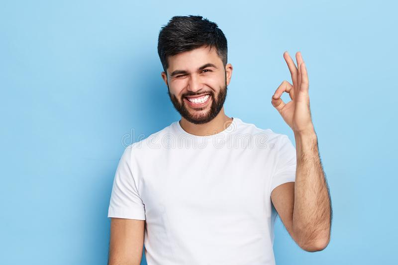 Happy cheerful bearded man winking his eye and showing ok sign stock photography