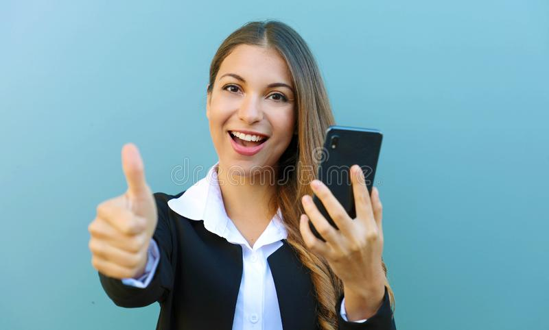 Happy cheerful business woman showing thumb up after reading good news on mobile phone outdoors royalty free stock photo