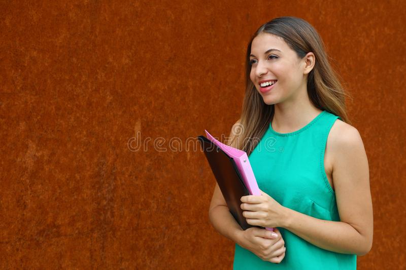 Happy cheerful business woman walking in the street holds folders and  looking to the side the copy space.  stock images