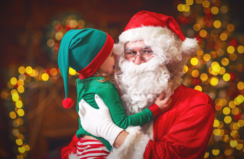 Happy cheerful child elf helper and Santa Claus at Christmas royalty free stock photos