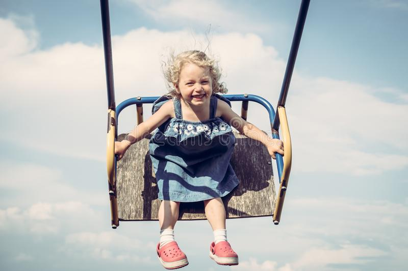 Happy cheerful child girl fun swinging sky happy carefree childhood royalty free stock images