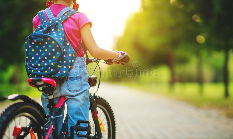 Happy cheerful child girl riding a bike in Park in nature. Happy cheerful child girl riding a bike in Park in the nature royalty free stock photography