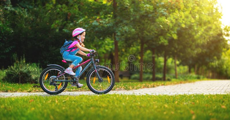 Happy cheerful child girl riding a bike in Park in nature. Happy cheerful child girl riding a bike in Park in the nature royalty free stock photos