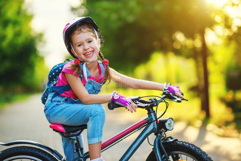 Happy cheerful child girl riding a bike in Park in nature. Happy cheerful child girl riding a bike in Park in the nature stock images