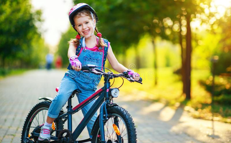 Happy cheerful child girl riding a bike in Park in nature. Happy cheerful child girl riding a bike in Park in the nature royalty free stock photo