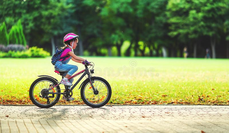 Happy cheerful child girl riding a bike in Park in nature royalty free stock photo