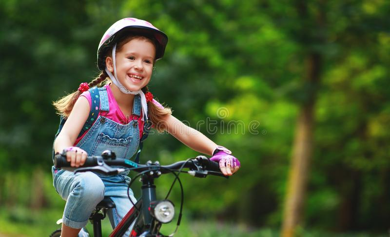 Happy cheerful child girl riding a bike in Park in nature stock image