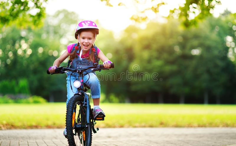 Happy cheerful child girl riding a bike in Park in nature. Happy cheerful child girl riding a bike in Park in the nature stock image