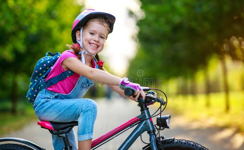 Happy cheerful child girl riding a bike in Park in nature stock photography
