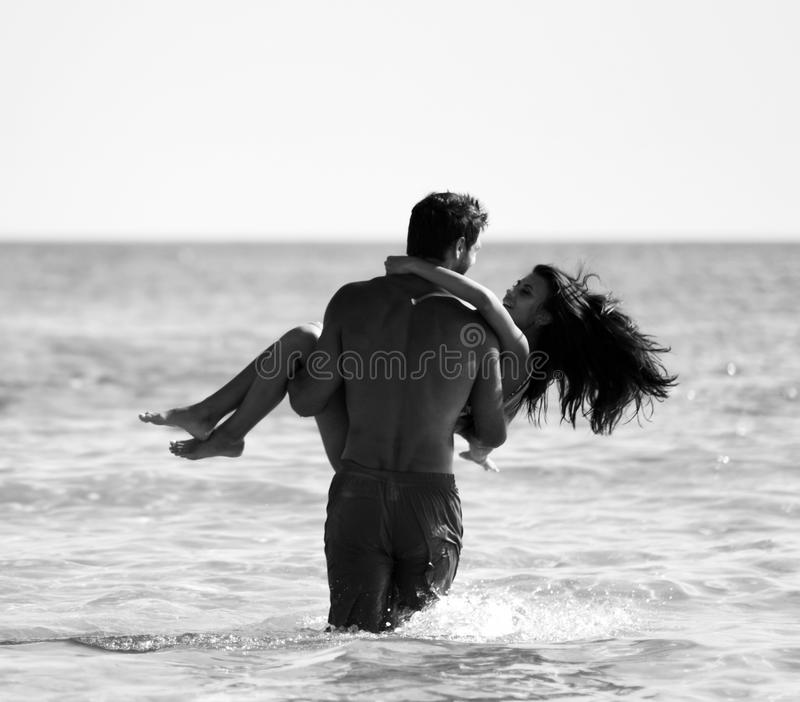 Happy cheerful couple having fun hugging running in the sea together. Romantic vacation, honeymoon love stock image