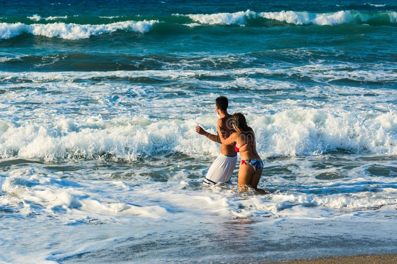 Happy cheerful couple having fun running and playing to the sea together and doing splashes of water stock image
